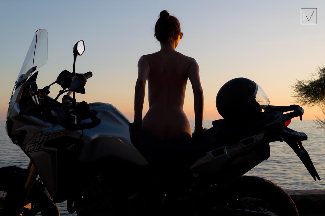 silhouette ragazza nuda sulla moto tramonto