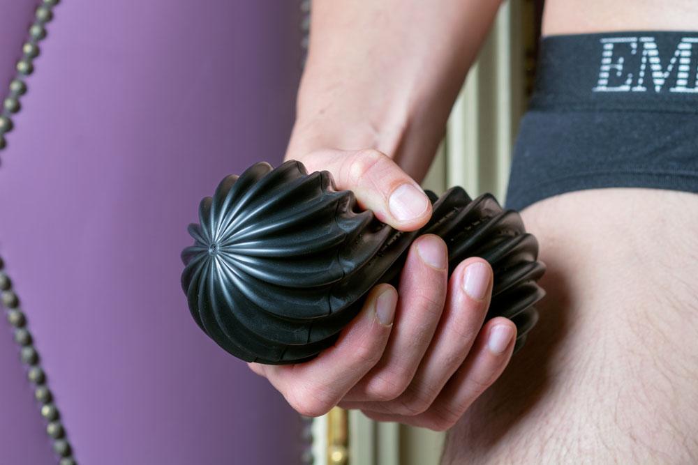 male hand holding sex toy tenga flex rocky black
