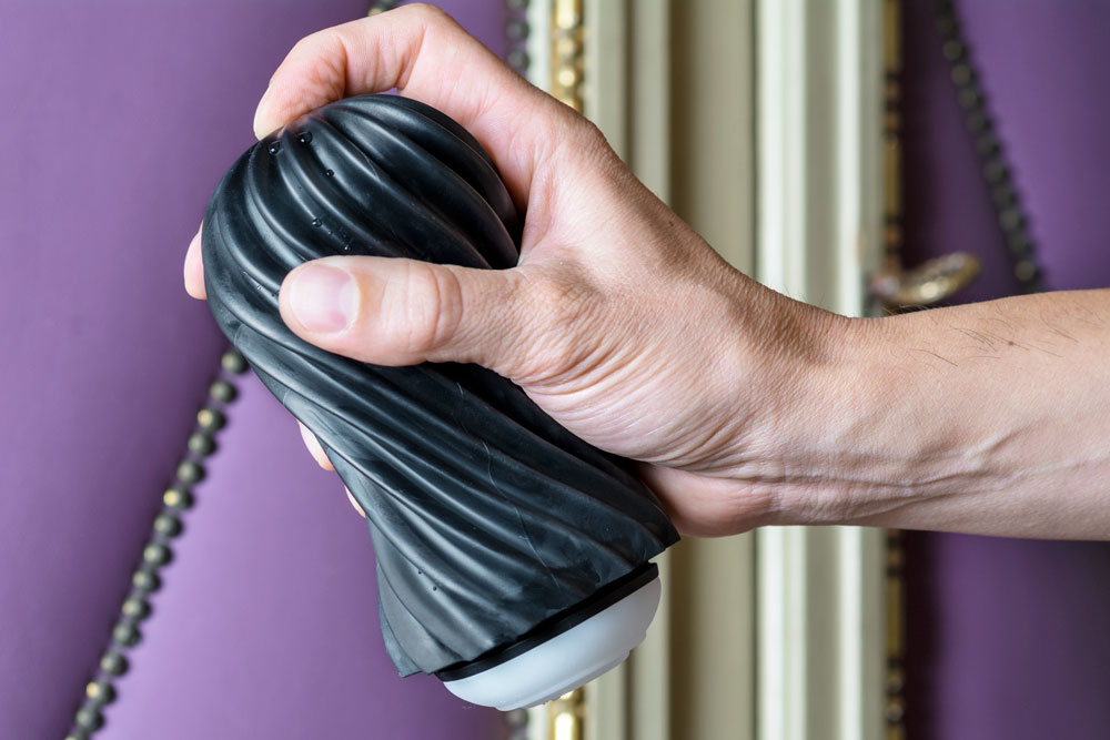 male hand covering the air hole of tenga flex rocky black sex toy