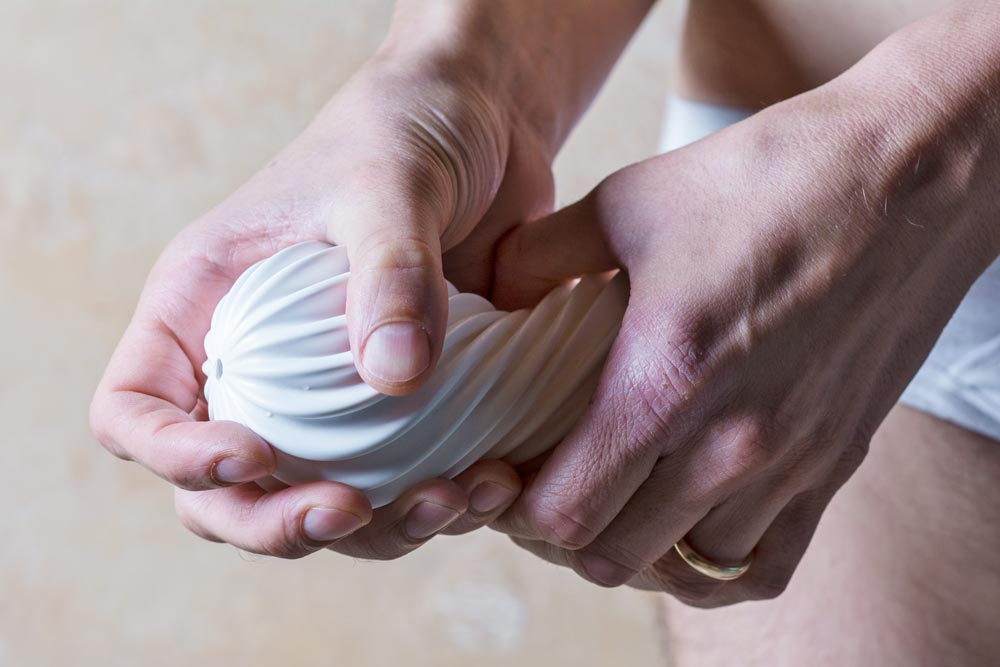 hands squeezing tenga flex silky white sex toy