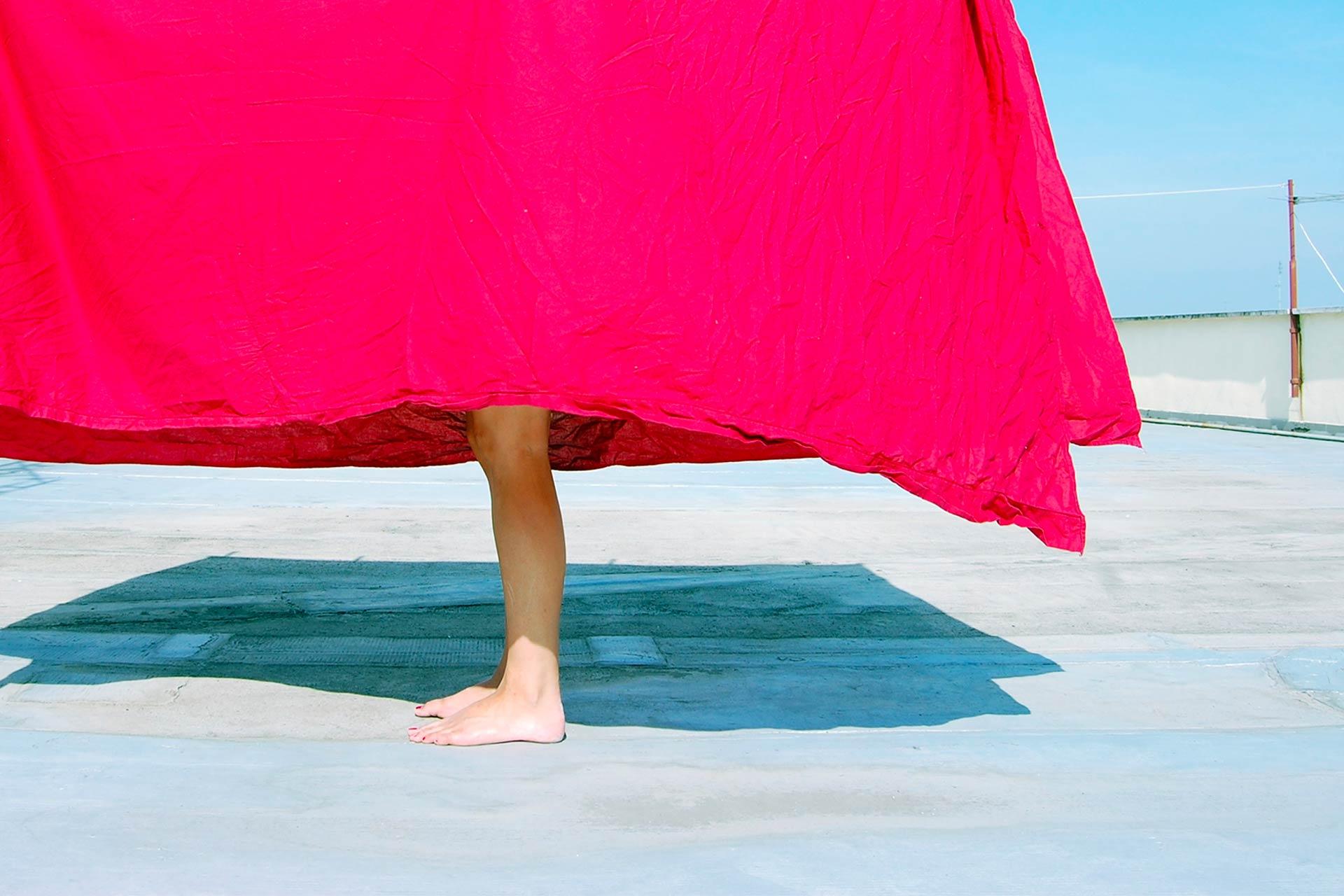 Piedi nudi che spuntano sotto le lenzuola stese sul terrazzo