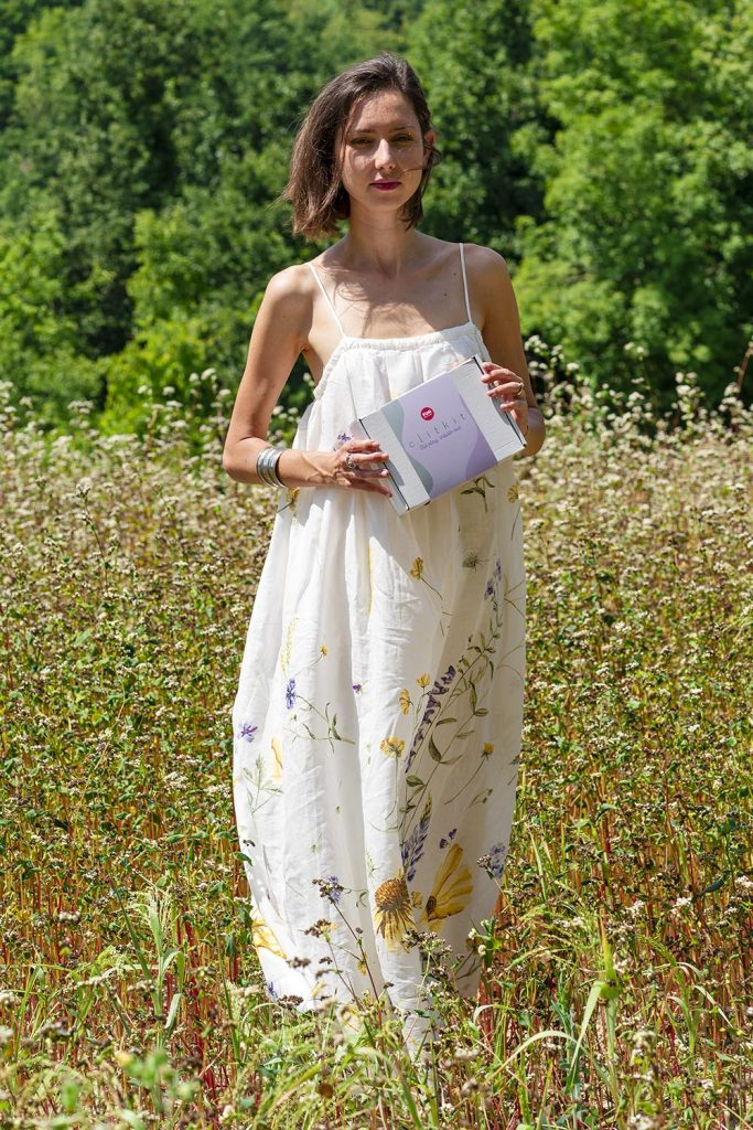 woman in fields with Fun Factory Clit Kit box